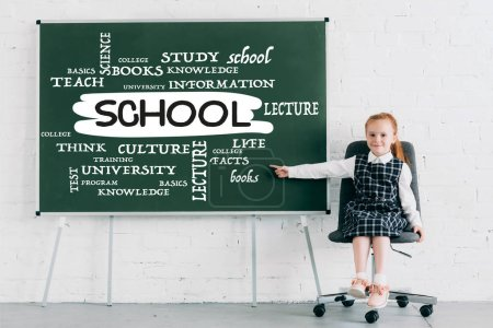 adorable little schoolgirl smiling at camera and pointing at chalkboard with school word