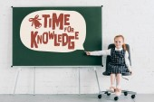 "adorable little schoolgirl smiling at camera and pointing at chalkboard with ""time for knowledge"" lettering in speech bubble"