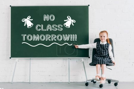 "adorable little schoolgirl smiling at camera and pointing at chalkboard with ""no class tomorrow"" lettering"