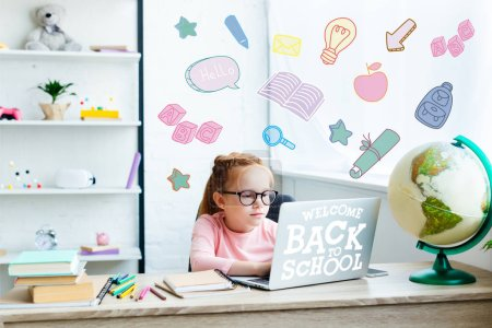 beautiful child in eyeglasses using laptop while studying at desk at home, welcome back to school