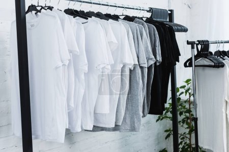 Photo for Selective focus of white, black and grey empty t-shirts on hangers in clothing design studio - Royalty Free Image