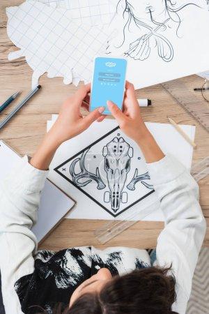 Foto de Vista aérea del diseñador femenino con smartphone con aplicación de Skype en pantalla a la mesa de trabajo con pinturas - Imagen libre de derechos