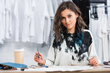 female fashion designer working at table with coffee cup in clothing design studio