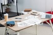 mise au point sélective de la table de travail avec la tasse de papier de café, de peintures et d'ordinateur portable
