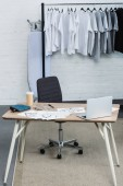 selective focus of t-shirts on hangers and working table with laptop and paintings in clothing design studio