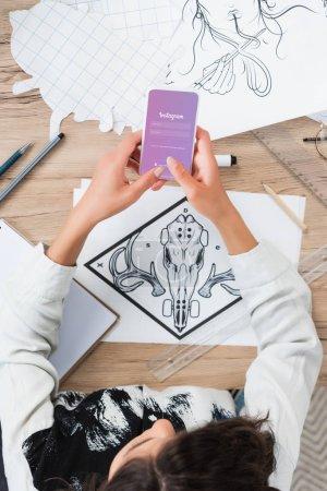 Photo pour Vue aérienne du concepteur femelle à l'aide de smartphone avec l'application instagram sur l'écran à la table de travail avec des peintures - image libre de droit