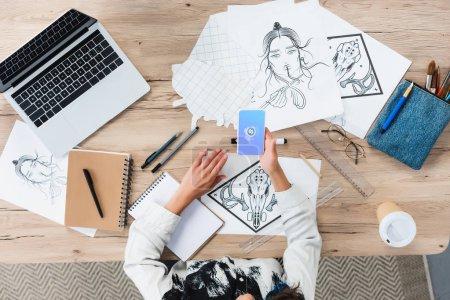 Photo pour Vue aérienne du concepteur femelle à l'aide de smartphone avec l'application shazam sur l'écran à la table de travail avec des peintures - image libre de droit