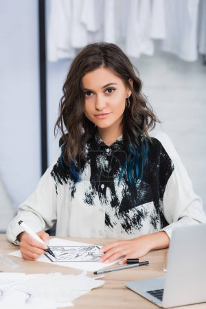 smiling female fashion designer painting at working table with laptop in clothing design studio