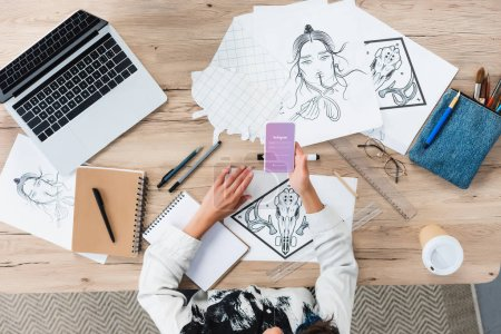 Photo for Overhead view of female designer using smartphone with instagram application on screen at working table with paintings - Royalty Free Image