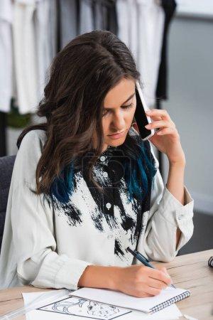 Photo pour Jeune designer de mode féminine, écrit en parlant manuels sur smartphone à la table de travail en studio de design de vêtements - image libre de droit