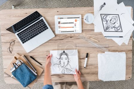 Photo for Cropped image of female designer putting painting on table with laptop and digital tablet with souncloud on screen - Royalty Free Image
