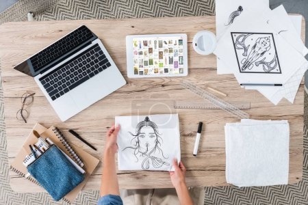 Photo for Cropped image of female designer putting painting on table with laptop and digital tablet with ebay on screen - Royalty Free Image