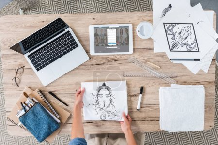 Photo for Cropped image of female designer putting painting on table with laptop and digital tablet with linkedin on screen - Royalty Free Image