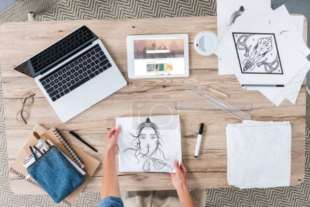 Photo for Cropped image of female designer putting painting on table with laptop and digital tablet with shutterstock on screen - Royalty Free Image