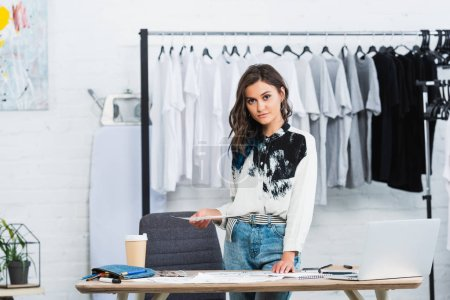 Photo for Attractive female fashion designer holding painting at table with laptop and coffee in clothing design studio - Royalty Free Image