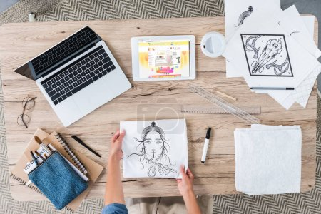 Photo for Cropped image of female artist putting painting on table with laptop and digital tablet with aliexpress on screen - Royalty Free Image