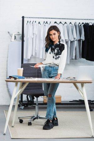 Foto de Joven diseñador mujer atractiva celebración de pintura en la mesa con el café en el estudio de diseño de ropa - Imagen libre de derechos