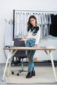 young attractive female designer holding painting at table with coffee in clothing design studio