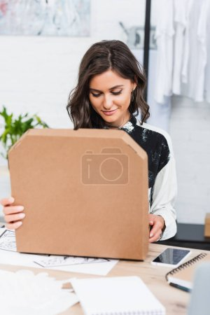 smiling female designer opening pizza box at table with smartphone