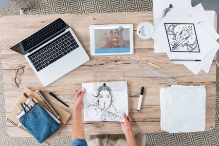 Foto de Imagen recortada de artista femenina poner pintura sobre mesa con ordenador portátil y tableta digital con couchsurfing en pantalla - Imagen libre de derechos