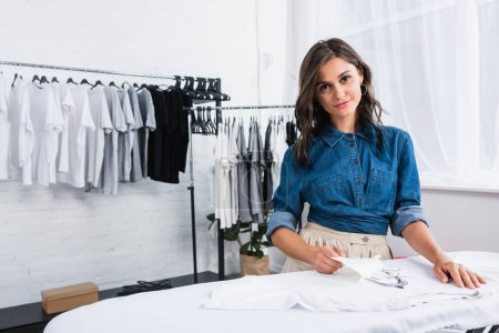 smiling young female fashion designer doing print on white t-shirt