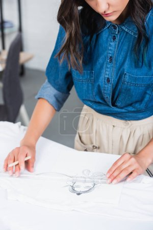 cropped image of female fashion designer measuring print on t-shirt by ruler