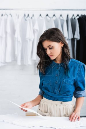young attractive female fashion designer choosing print for empty white t-shirt in clothing design studio