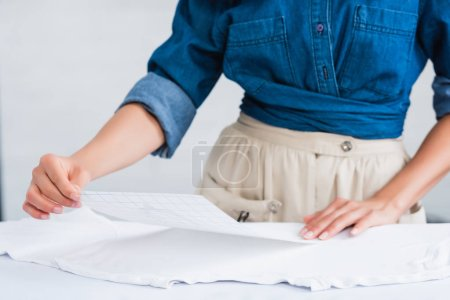 cropped image of female fashion designer choosing print for empty white t-shirt