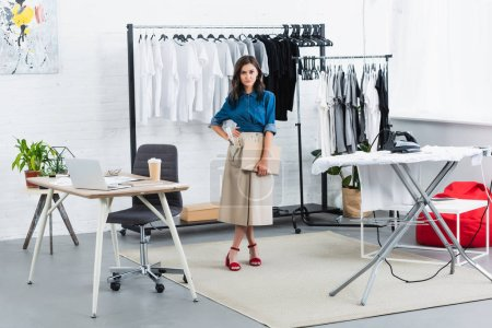female fashion designer standing with textbook in clothing design studio