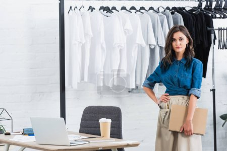 attractive female fashion designer standing with textbook near table with laptop and coffee in clothing design studio