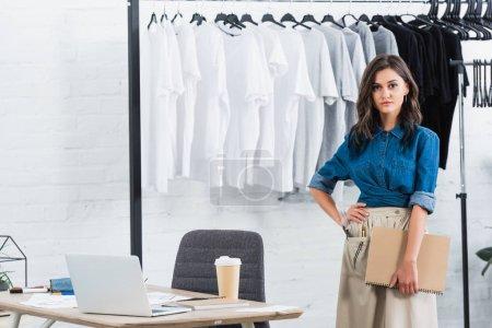 Photo pour Attrayant femme styliste permanent avec manuel près de table avec ordinateur portable et le café dans le studio de design de vêtements - image libre de droit