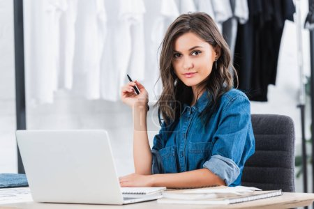 smiling attractive female designer working at table with laptop