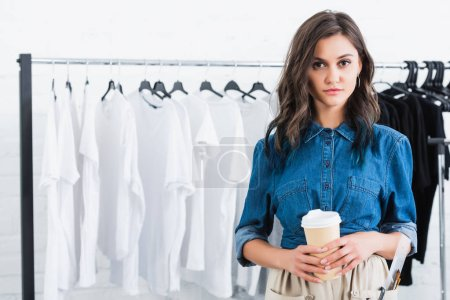 young female fashion designer holding coffee cup in clothing design studio