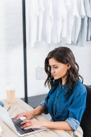 selective focus of female fashion designer working at table with laptop in studio
