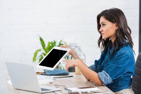 Photo pour Vue latérale de la jeune femme pointant sur une tablette numérique avec écran blanc à table - image libre de droit