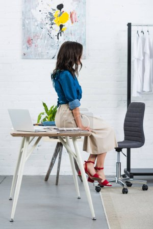 side view of female fashion designer sitting on table in clothing design studio