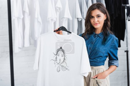 Photo for Young female fashion designer showing white t-shirt with print in clothing design studio - Royalty Free Image