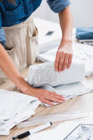 cropped image of female fashion designer folding t-shirt at table in clothing design studio