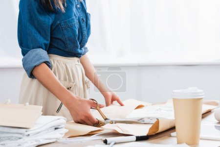 Photo for Cropped image of female fashion designer wrapping t-shirt with print in paper package at table with coffee cup - Royalty Free Image