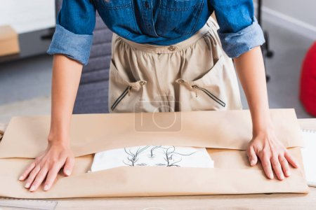 cropped image of female fashion designer wrapping t-shirt with print in paper package at table