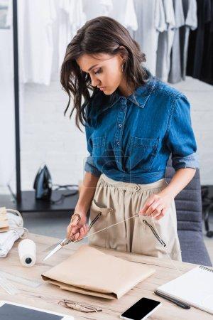 Foto de Cuerda de envoltura corte de diseñador de moda femenina para el paquete sobre la mesa en el estudio de diseño de ropa - Imagen libre de derechos