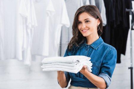 smiling female designer holding stack of white t-shirt in clothing design studio