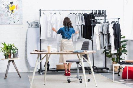 rear view of female designer taking black t-shirt from hanger in clothing design studio