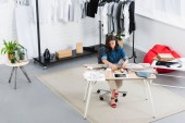 high angle view of female fashion designer painting on jacket at working table in clothing design studio