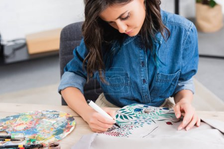 selective focus of female fashion designer painting on jacket at working table in clothing design studio