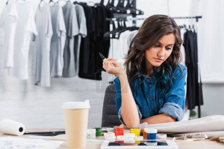 Photo for Female fashion designer painting on jacket at working table with coffee cup in clothing design studio - Royalty Free Image