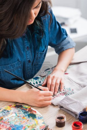 focused female fashion designer painting on jacket at working table in clothing design studio