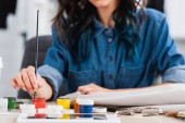 cropped image of female fashion designer painting on jacket at working table in clothing design studio