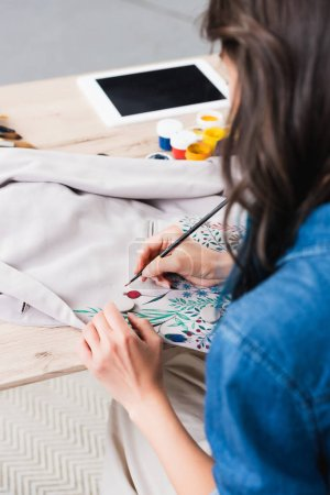 female fashion designer painting on jacket at working table in clothing design studio