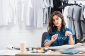 young female fashion designer sitting at working table with paints an coffee